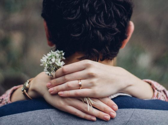 woman's hand on man's shoulder in close up photo