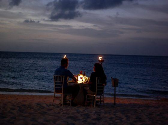couple sitting at seashore having dinner date