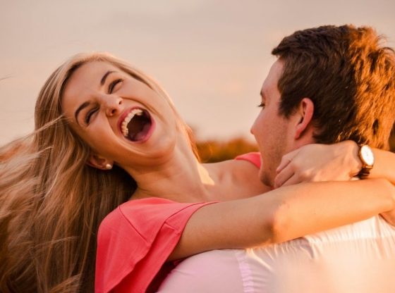 man hugging woman while smiling