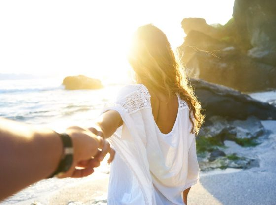 Person holding woman's hand beside sea while facing sunlight.