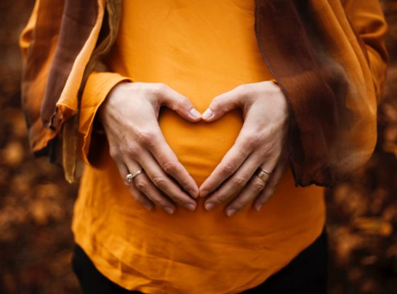 woman making a heart out of her hands over her pregnant stomach