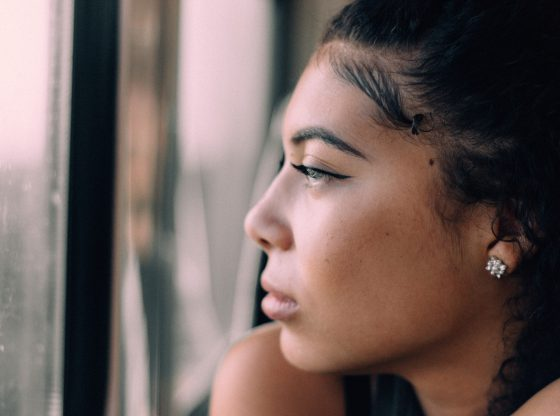 pensive woman stares out the window