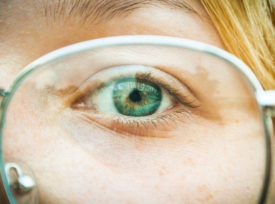 green eye behind glasses