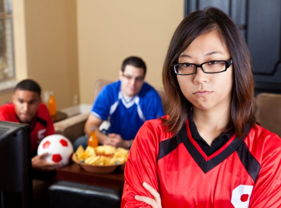 Young woman upset at men watching sports on TV