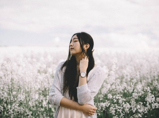 east asian woman standing in field of white flowers