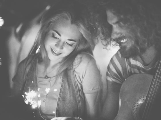 Young hipster couple on a date celebrating with sparklers