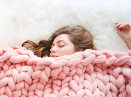 woman sleeping under knitted blanket