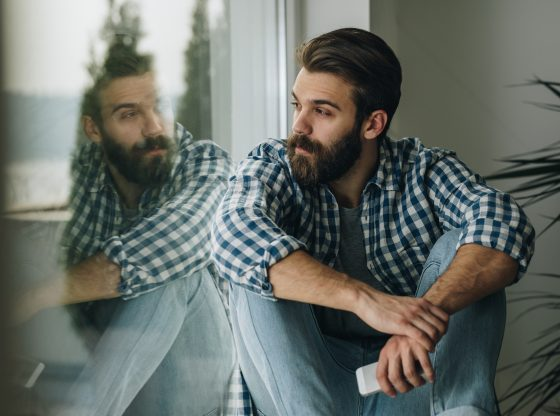 pensive man looks out window