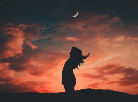 silhouette of woman under new moon and orange sky