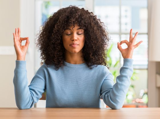 African american woman at home relax and smiling with eyes closed doing meditation gesture with fingers.