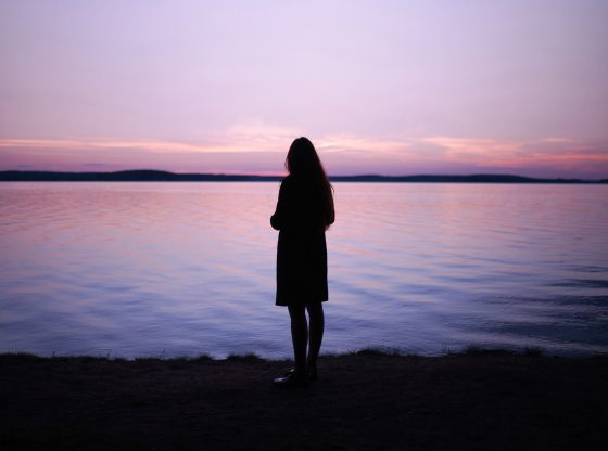 silhouette of woman looking out at lake