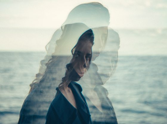 overlay of woman staring intensely by ocean