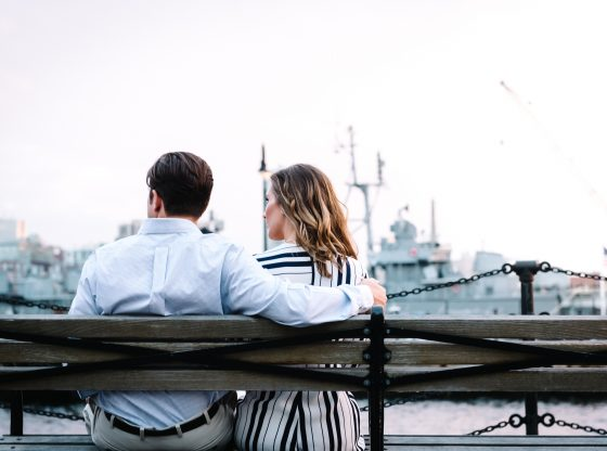 couple sitting on bench near body of water