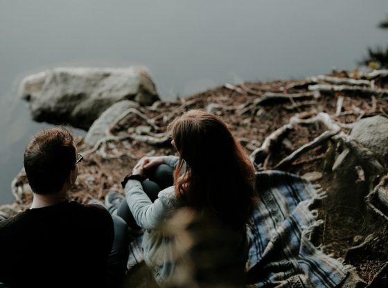 couple sitting near the body of water