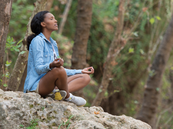 woman meditating on rock