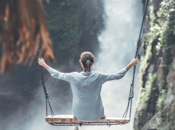 woman swinging near waterfall