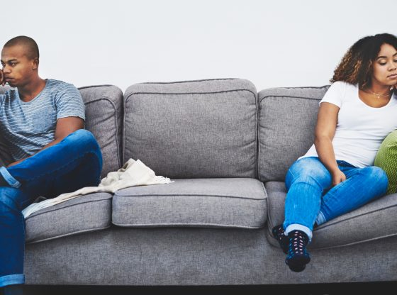 young couple sitting on opposite sides of the couch