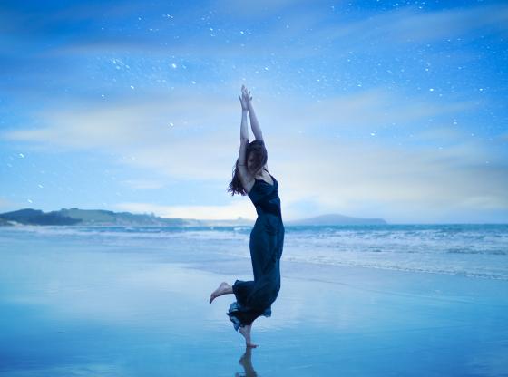 woman dancing on beach under stars