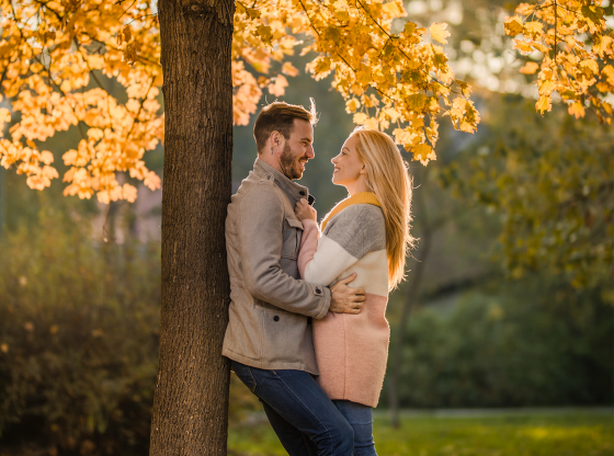 couple-leaning-against-tree-under-fall-leaves