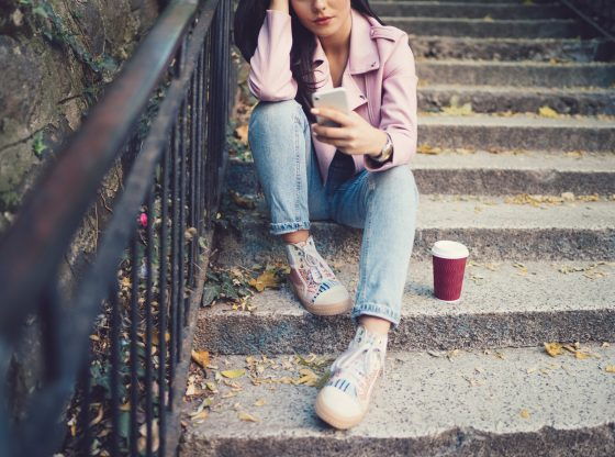 girl sitting on stairs with cellphone