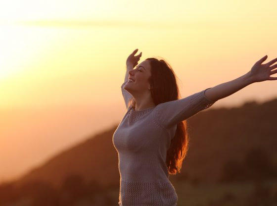 woman with arms spread at sunset