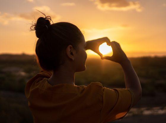 woman makes hand heart over sun