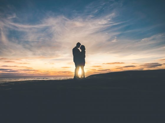 Silhouette of two people standing closely in front of the setting sun