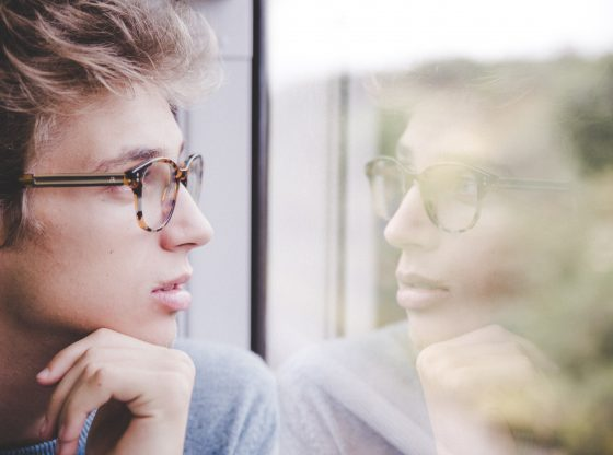 Man with glasses looking out window