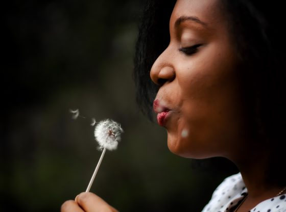woman wistfully blowing a dandelion