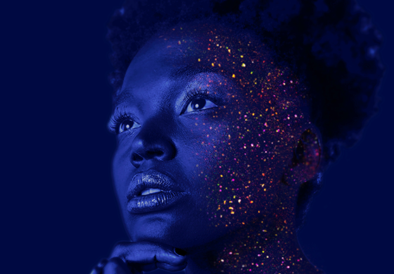 woman in blue lighting with glitter