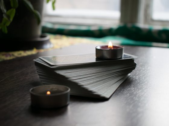 A splayed deck of cards on a table, surrounded by candles.