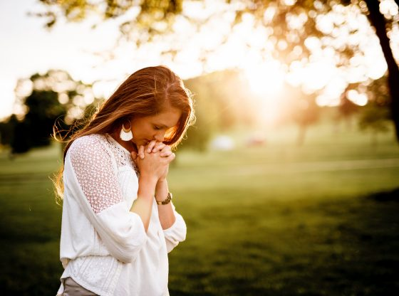 grateful woman praying in park