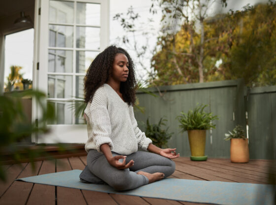Young woman sitting in the lotus pose outside on her patio